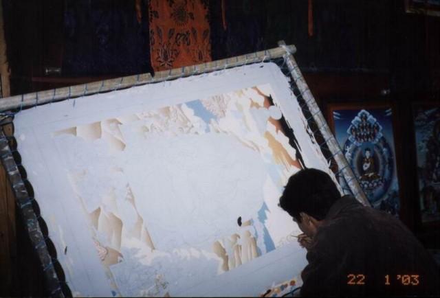 Рисует тибетскую тханку.