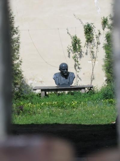Ленин коротает дни на старой лавочке где-то за сарями Елагинского дворца. Снято через дыру в заборе.
