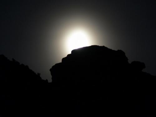 Луна нереально огромная выползает над скалами.