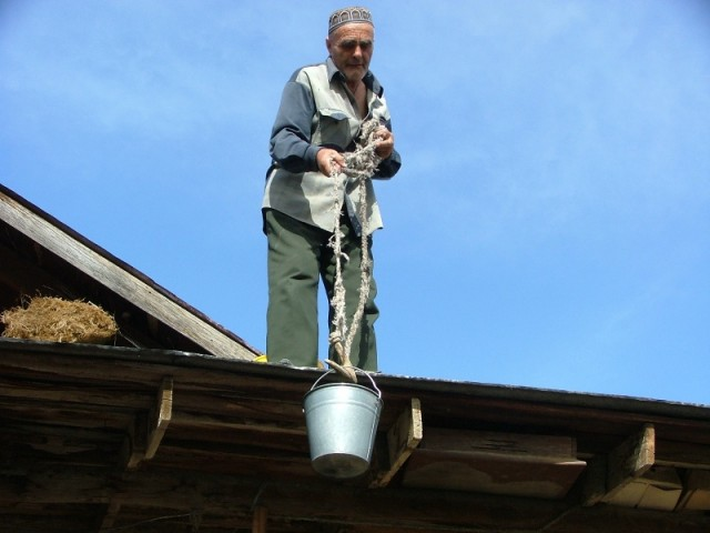 Старик поднимает воду на крышу, не поняла зачем...