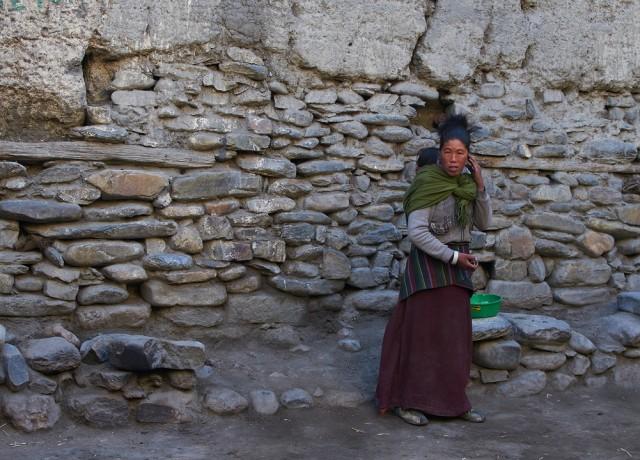 Женщина на фоне городской стены