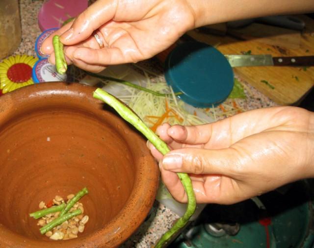 Чили, чеснок, арахис, помидоры, стручковая фасоль, сок лайма встречаются в ступке