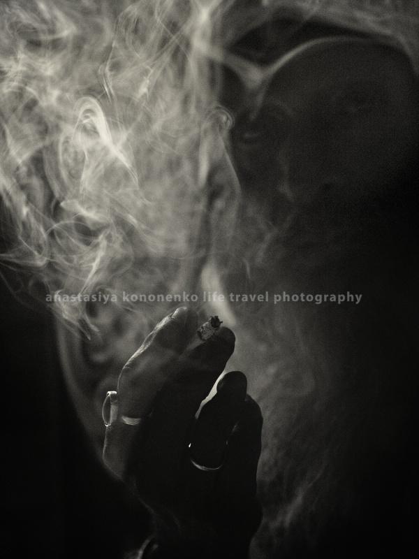 в пасмурный день. Курит.