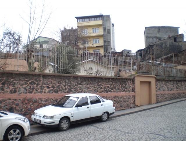 Фасад Церкви виднеется за забором с колючей проволокой)