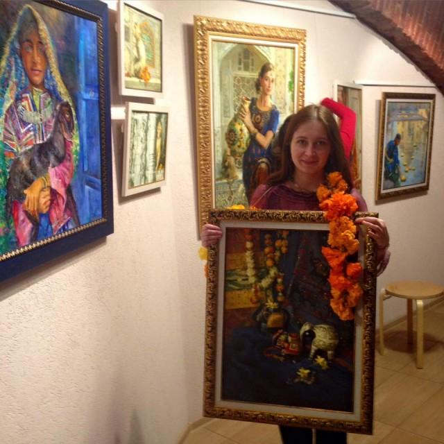 Анастасия Вострецова развешивает картины перед выставкой