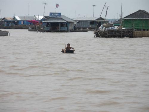 мальчик из плавучей рыбацкой деревушки вышел в тазике нас поприветствовать