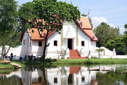 Тайцы общаются в тени храма