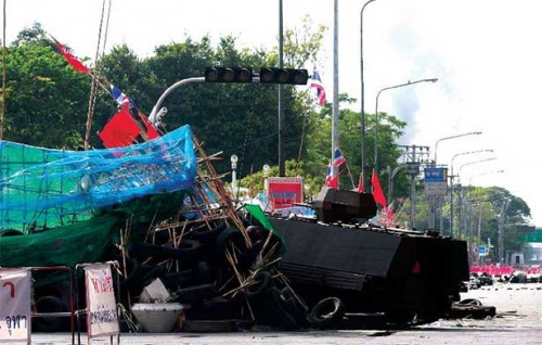 An armoured personnel carrier brings down a red shirt barricade at Sala Daeng Intersection