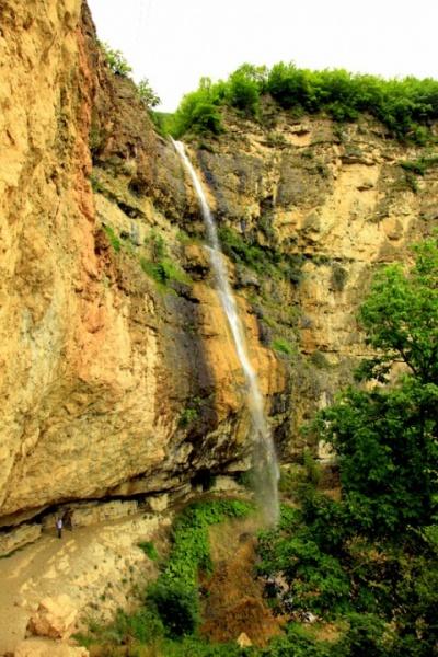 Человек у подножия гор и водопада