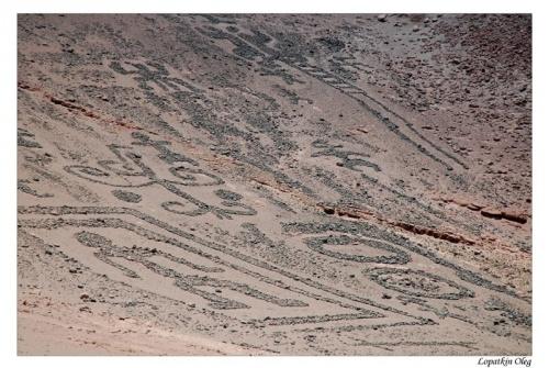 петроглифы на склоне холма (величина каждого около 10-15 метров)