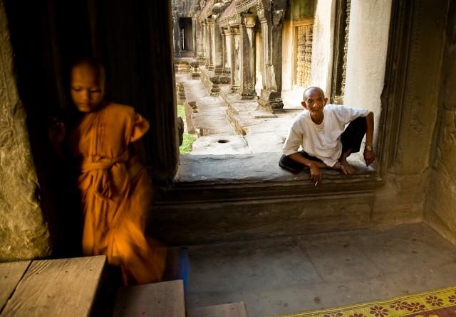 Маленький буддийских монах ухаживает за статуей будды в помещении Ангкора