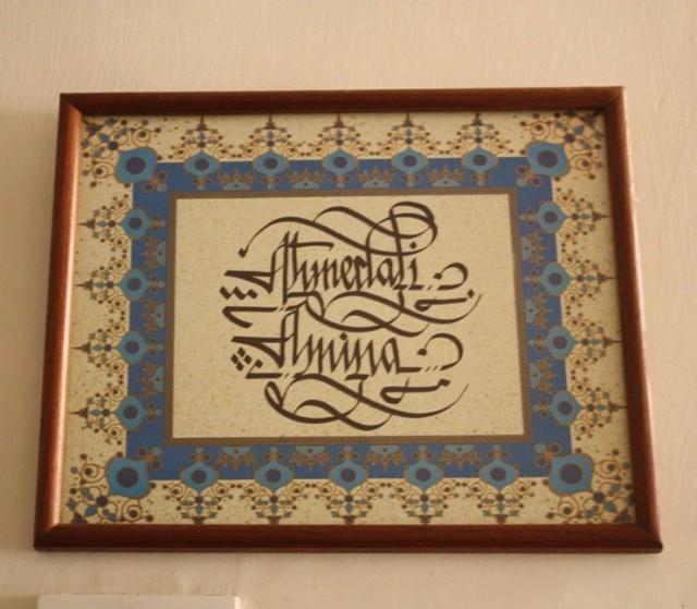 Ахмедали и Амина написано каллиграфией перед входом в дом.