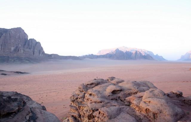маленькая фигурка на камне - затерявшийся человек в безбрежности пустыни