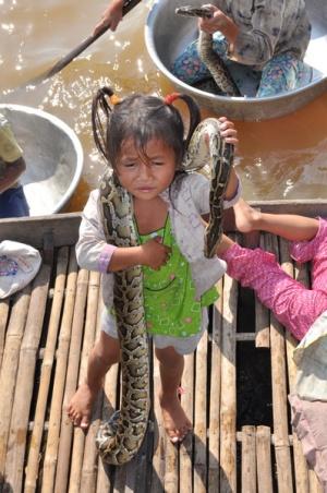 Плавучая деревня на озере Тонлесап. Мать только что наругала девчушку за то что та пыталась спрятать змею в подполье лодки. Arbeiten!