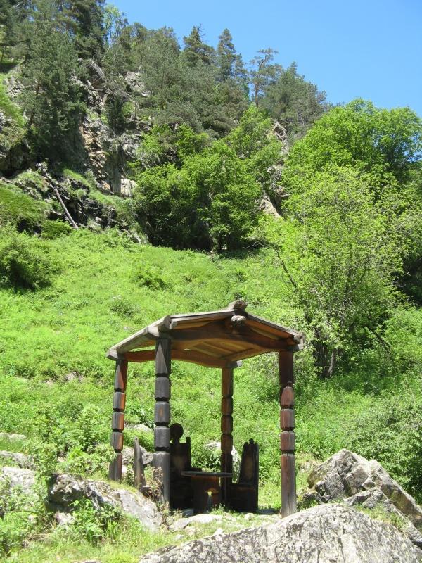 Чуть выше находится беседка с тремя резными креслами и столиком. Здесь паломники оставляют свои пожертвования - монетки, в основном.