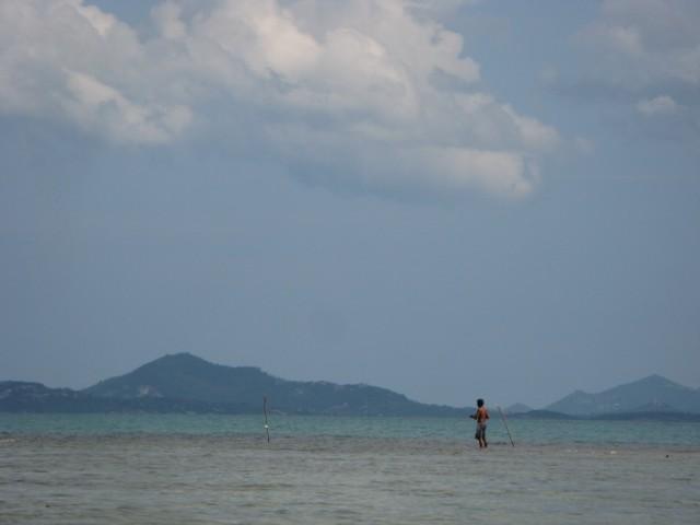 Рыбак на рифе и Ко Самуи на горизонте