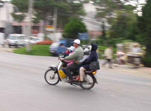 Обычное дело для Вьетнама. 4 человека на мотобайке, все семья. А законом запрещена езда больше двух человек. Но кто смотрит эти правила?