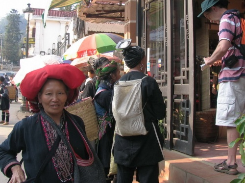 женщина Дзао и редкая эническая группа с антенами на голове торгуются с туристами