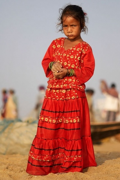 девочка из рыбацкой деревне в очень ярком платье, явно обиженная на своих родителей