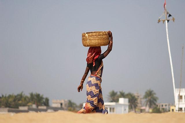 женщина с корзиной возвращается в свою рыбацкую деревеньку