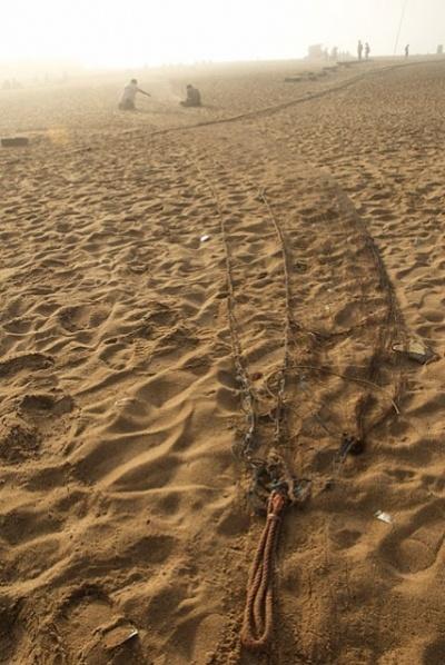 утром рыбаки вытаскивают сети на берег, достают рыбу и ремонтируют сети (зашивают дыры) :)