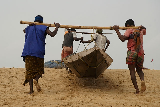 рыбаки несут лодку к морю