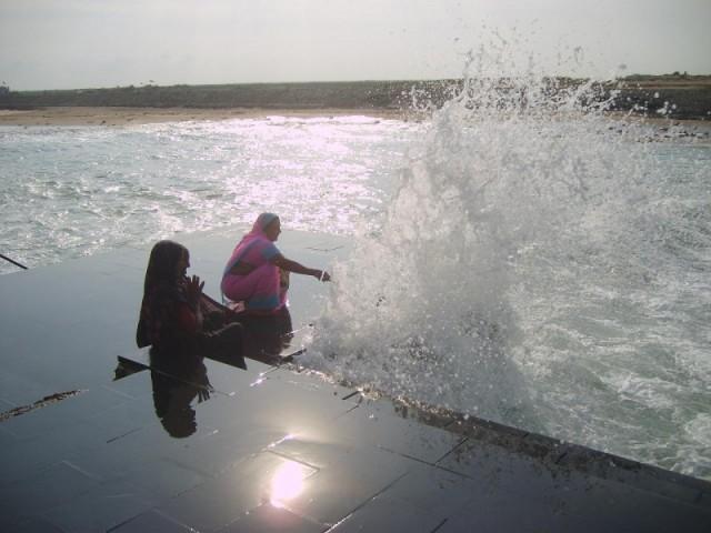 Купание индусок в Дварке брызгами набегающих волн