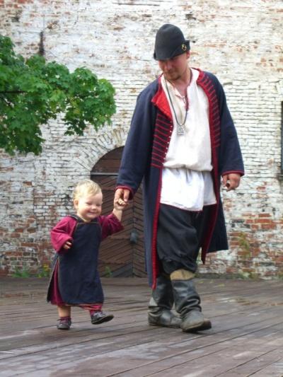 Молодые люди ходят, одетые в костюмы той эпохи