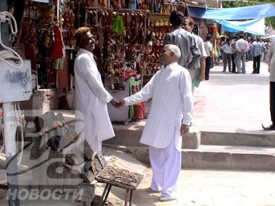 Приветствие двух коллег-продавцов на рынке в Джайпуре