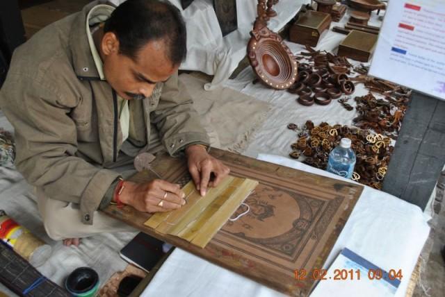 Художник показывает технику гравировки с чернением на пальмовом листе