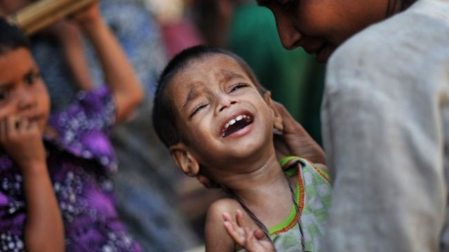 A Muslim Rohingya mother comforts her crying child as they wait for medical care at a clinic in Rakhine, Myanmar on November 2