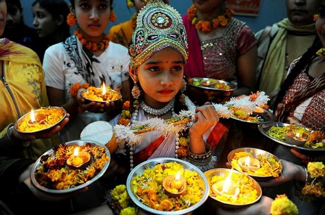 Девочка в костюме индийской богини Сарасвати принимает участие в фестивале весны в Амритсаре