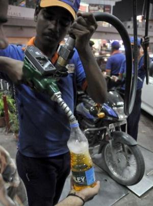 Из-за повышения цен на бензин, мотоциклист покупает дополнительное топливо. Хайдарабад, вечером во вторник